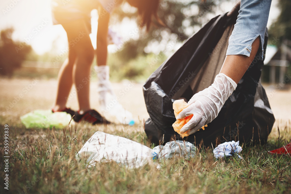 Fototapeta woman hand picking up garbage plastic for cleaning at park