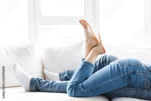 Deurstickers Ontspanning Cropped portrait of male and female legs, young couple hugging together while lying on sofa at home