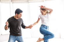 Portrait Of Joyful Couple Laughing And Dancing While Having Fun At Home