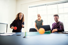Laughing Young Designers Playing Table Tennis On A Boardroom Tab