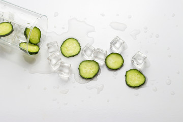Spilled Glass with refreshing water, cucumber slices and ice cubes on a light background