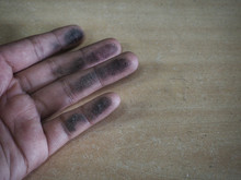 The Fingers Of The Person Who Touches The Wooden Table That Is Full Of Black Dust Makes The Fingers Dirty.