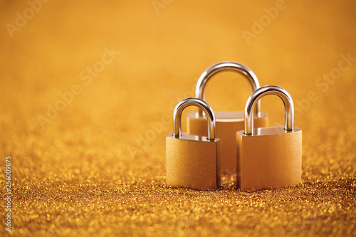 Photographie  Security concept with three metal padlocks over golden background