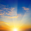 Scenic sunset with sun rays against bright blue sky