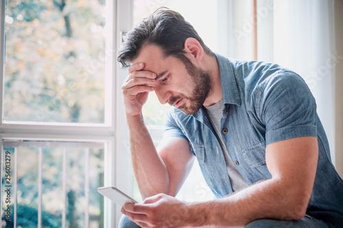 Obraz na płótnie Worried man watching smartphone and waiting message