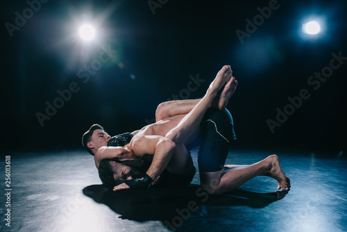 Photo  mma fighter doing chokehold and joint lock to another sportsman during submissio