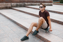 Attractive Young Hipster Man In Dark Sunglasses In Summer Fashionable Clothes In Sneakers Sits On A Skateboard In The City On A Warm Summer Day. Sports Guy Teenager.