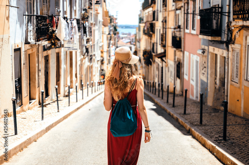 Foto  Young traveling woman walking on the streets of Lisbon city and looking at beaut