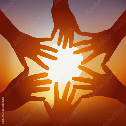 Concept de l'adhésion d'un groupe avec cinq mains tendues devant un coucher de soleil, pour symboliser l'union et la cohésion Wallpaper Mural