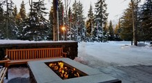 Sunrise/Sunset In A Rustic Outdoor Setting, With Gorgeous Modern Fire Pit In Foreground And A Snow Covered Evergreen Background