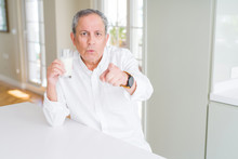Handsome Senior Man Drinking A Glass Of Fresh Milk At Breakfast Pointing With Finger To The Camera And To You, Hand Sign, Positive And Confident Gesture From The Front