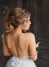 Charming Tender Princess Stands With Her Back To Camera, Soft Features With Professional Make-up, Magnificent White Amazing Dress With Open Back And Shoulders For Prom High School Graduation 2019