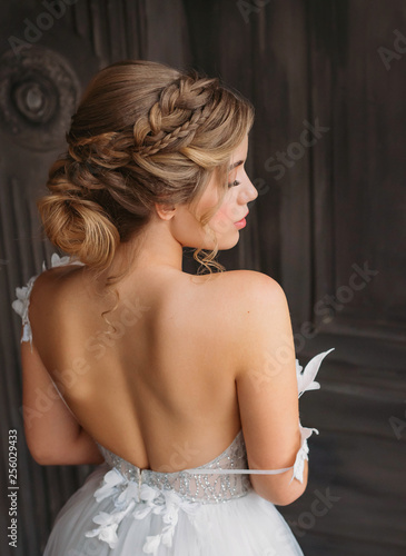 charming tender princess stands with her back to camera, soft features with professional make-up, magnificent white amazing dress with open back and shoulders for prom high school graduation 2019 Fotomurales