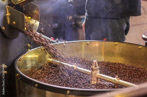 Freshly roasted aromatic coffee beans in a modern coffee roasting machine - 256034066