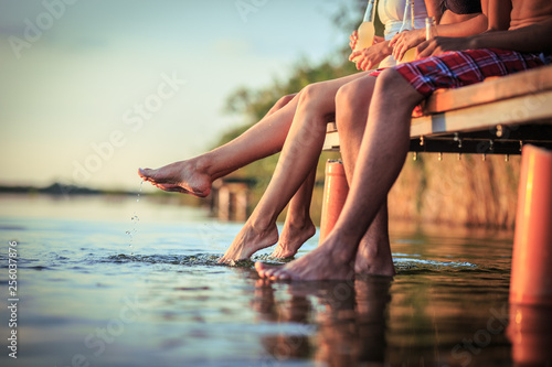 Fotografie, Obraz Group of friends sitting and having fun on the pier by the lake on sunset