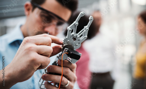 Fotomural A young businessman or scientist with robotic hand standing in office, working