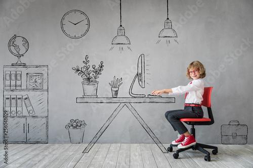 Fotografie, Obraz  Happy child sitting at the desk in imaginary office