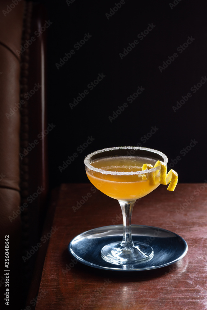 Fototapeta Sidecar Cocktail Served Straight Up with Sugared Rim in Dark Luxurious Bar or Restaurant
