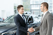 Congratulations. Horizontal portrait of a young businessman shaking hands with the car dealer after a successful deal
