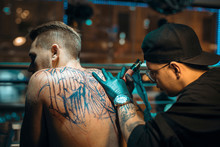 Side View Of Male Tattoo Artis...