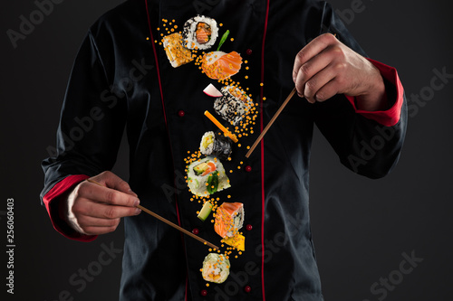 Photo  Master chef holding chopsticks with flying sushi