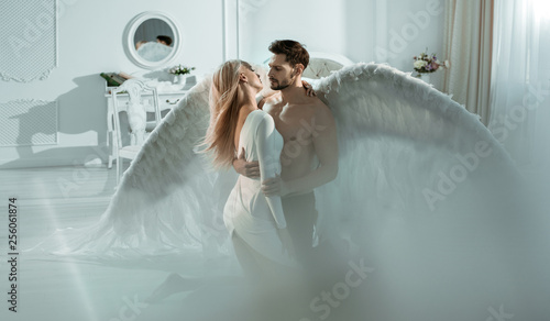 Foto  Conceptual portrait of an archangel embracing a beautiful woman
