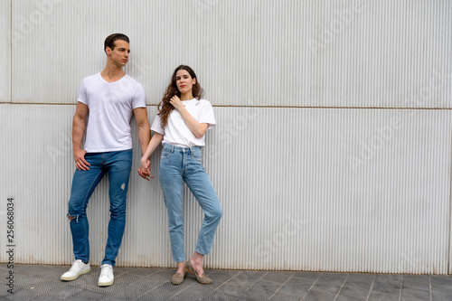 Printed kitchen splashbacks Artist KB Happy Couple Leaning Against Wall Holding Hands wearing casual clothes in a bright day