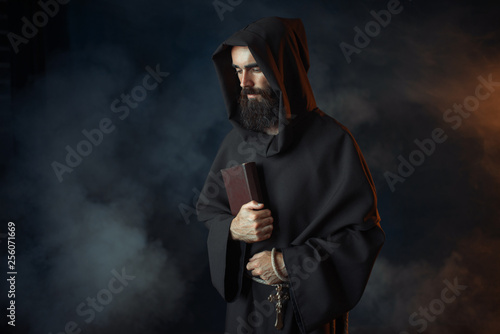 Fototapeta Medieval monk in robe holds spellbook in hands