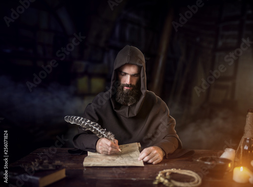 Foto Medieval monk in robe writes with a goose feather