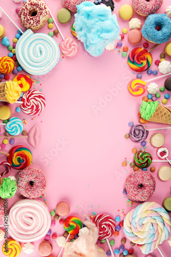 candies with jelly and sugar. colorful array of different childs sweets and treats on pink