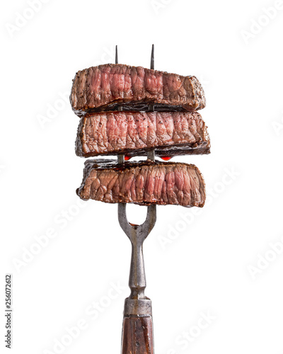 Slices of beef steak on vintage fork isolated on white Canvas Print