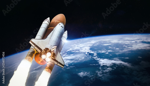Space shuttle launch in outer space from Earth. Rocket on orbit of the planet. Elements of this image furnished by NASA - 256073456