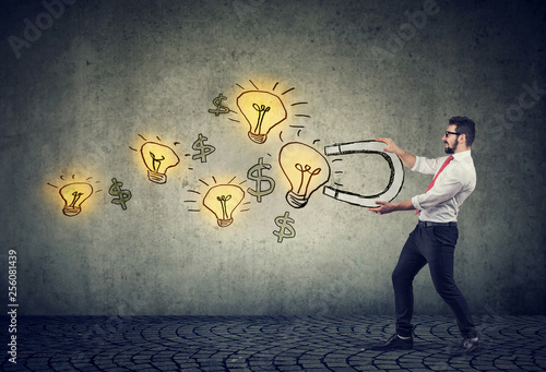 Photo Business man attracts bright ideas light bulbs with a magnet