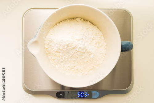 Fotografie, Obraz  Step by step recipe to prepare a tasty challah, 500 grams , 18 oz or 4 cup of all purpose flour,  on a big porcelan jar, top view over a yellow background, check the ther image of the series