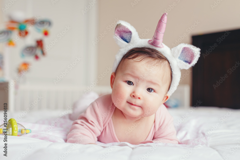 Fototapety, obrazy: Portrait of cute adorable Asian mixed race smiling baby girl four months old lying on tummy on bed in bedroom wearing unicorn headband horn and ears looking in camera.