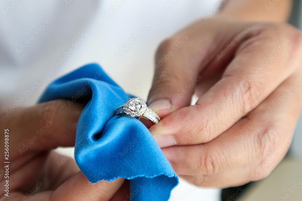 Fototapeta Jeweller hand polishing and cleaning jewelry diamond ring with micro fiber fabric