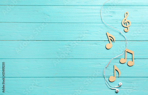 Flat lay composition with music notes, earphones and space for text on color wooden background - 256101230