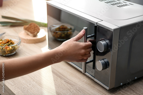 Fototapeta Young woman using microwave oven on table in kitchen obraz
