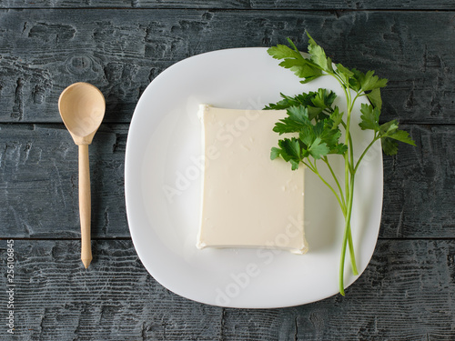 Tuinposter Restaurant A piece of Serbian cheese with parsley and a wooden spoon on a black table. The view from the top. Dairy product.