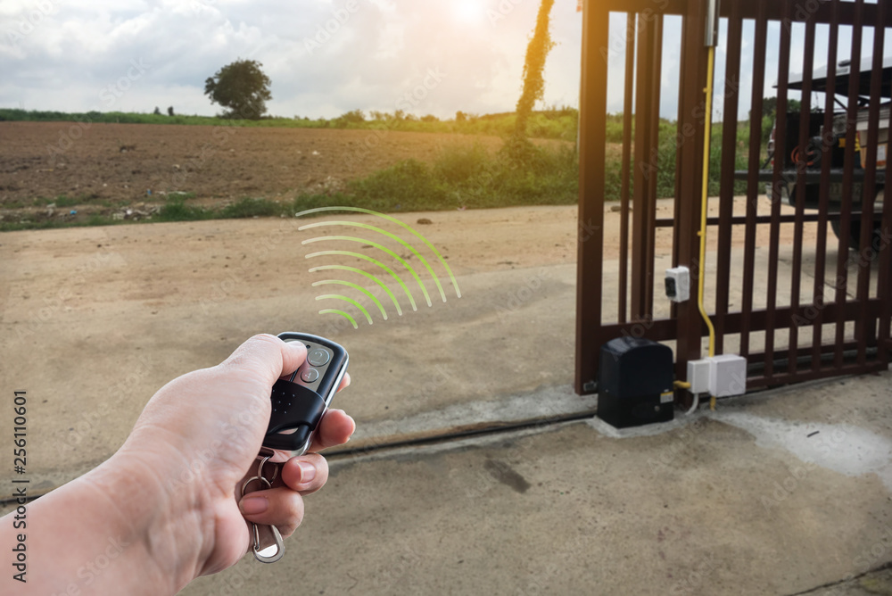 Fototapeta Signal of remote control when person open automatic gate at house for home security system with sunlight rays
