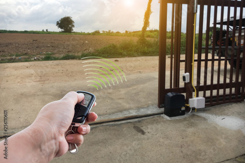 Obraz Signal of remote control when person open automatic gate at house for home security system with sunlight rays - fototapety do salonu