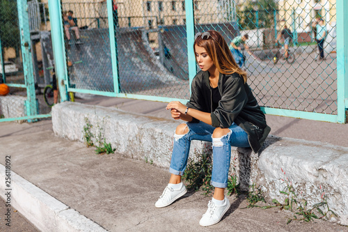 Leinwand Poster Fashion portrait of trendy young woman wearing sunglasses, and bomber jacket sit