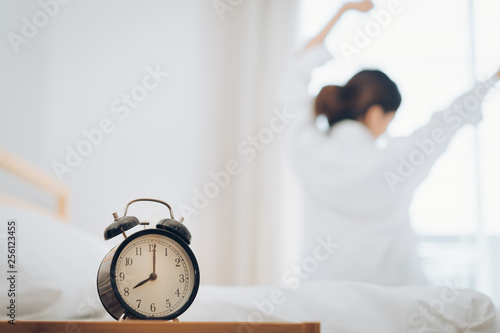 Obraz Woman wake up with alarm clock at moring her stretch on bed at home. - fototapety do salonu