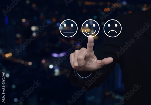 Fotografie, Obraz  Businessman pressing excellent smiley face rating icon over blur colorful night