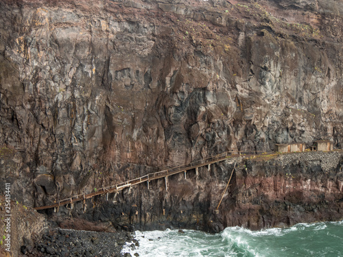 thrilling wooden bridge on a cliff at the coast near Ponta de Sao Jorge on the island of Madeira, Portugal #256134411