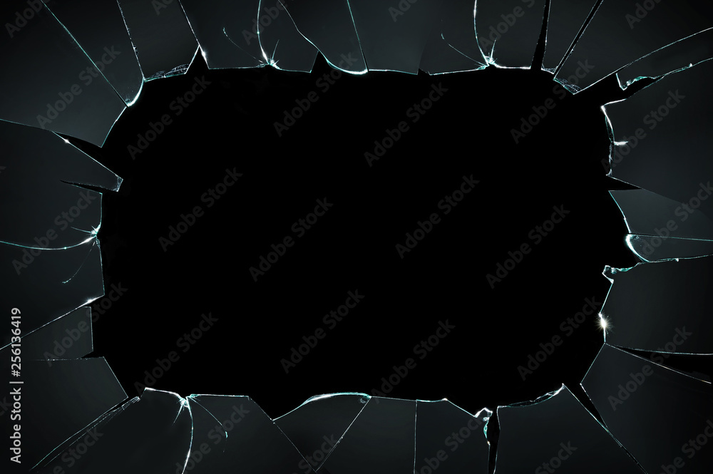 Fototapeta broken cracked glass with big hole over black background