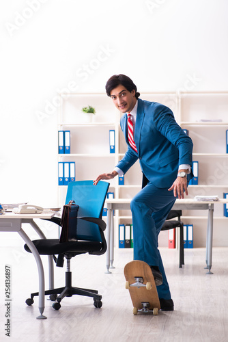 Fototapety, obrazy: Young handsome businessman with longboard in the office