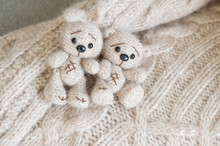 A Knitted Beige Bunny And Bear Are Lying On The Plaid Handmade Of The Same Color.