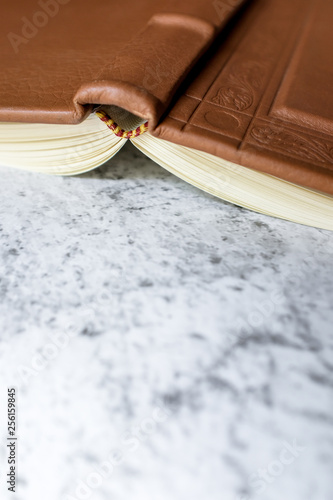 Fotografia Brown leather vintage notebook blank pages open upside down on bright white and gray concrete color texture table top with empty copy space