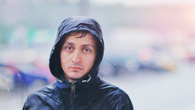 Portrait Of A Young Man In A Jacket With A Hood In The Rain On Blurred Background City Street, Close-up